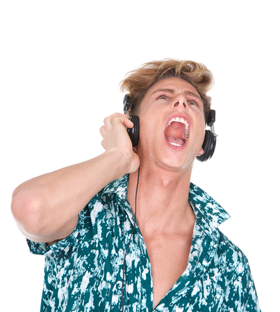 Close up portrait of a young man singing while listening to music on headphones  photo