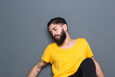 Portrait of a handsome guy with beard sitting against gray background photo