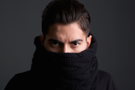 intimidating: Close up portrait of an intimidating young man with scarf covering face