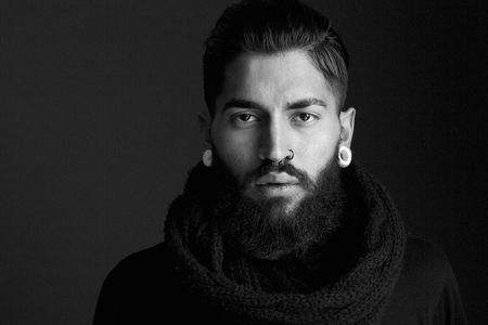 Black and white close up portrait male fashion model with beard and piercing
