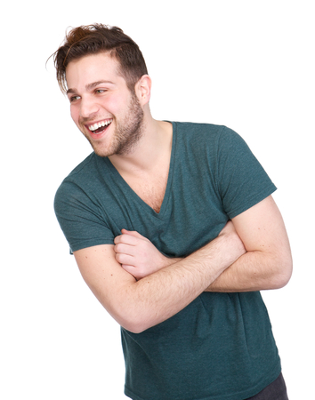 Close up portrait of a young man smiling with arms crossed on isolated white background