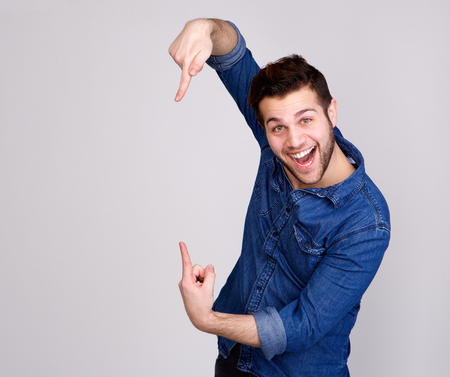 isolated on gray: Portrait of a handsome young man smiling and pointing to copy space on isolated gray background Stock Photo