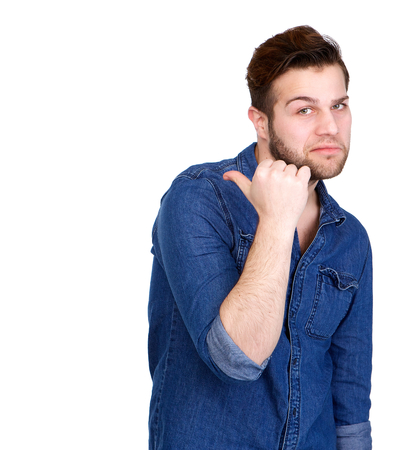 and decline: Portrait of a young man with frown showing thumb pointing behind on isolated white background Stock Photo