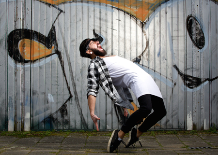 Portrait of a modern male dancer with beard posing against graffiti wall outdoors photo