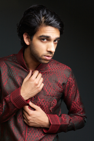 Close up portrait of a young indian man wearing traditional indian clothing on gray background photo
