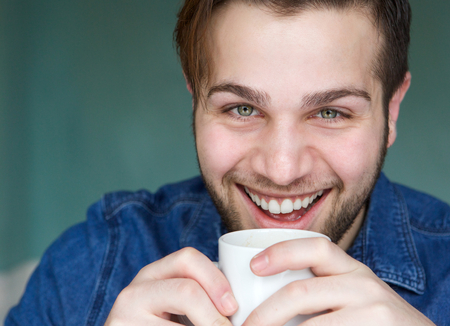 Close up portrait of a handsome young man drinking cup of coffee photo