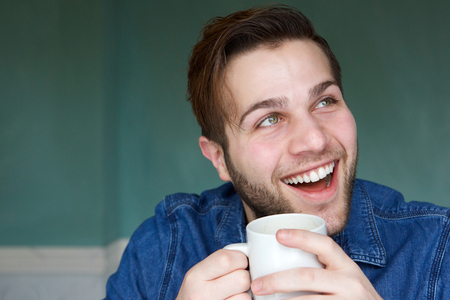 Close up portrait of a young man smiling with cup of coffee photo