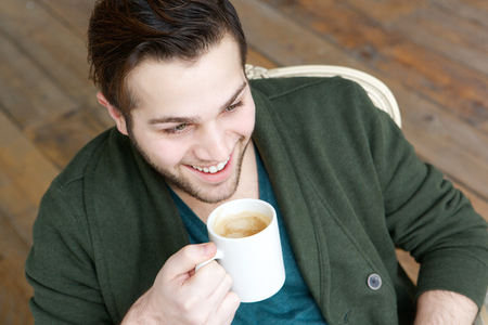 Close up portrait of a handsome young man relaxing at home with cup of coffee  photo