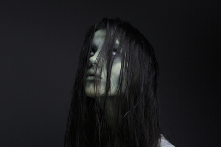 Close up portrait of a female zombie on black background Stock Photo