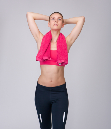 isolated on gray: Portrait of a beautiful young woman looking up with hands behind head, relaxing after exercise workout on isolated gray background