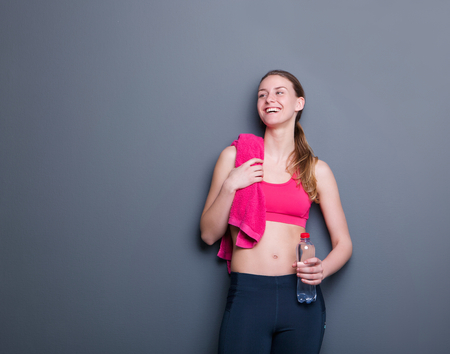 Portrait of a healthy young woman smiling with water bottle and towel after work out 版權商用圖片