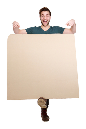 Full length portrait of a young smiling man pointing finger down to blank poster board on isolated white background photo