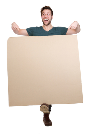 Full length portrait of a cheerful young man smiling and pointing to empty poster on isolated white background photo