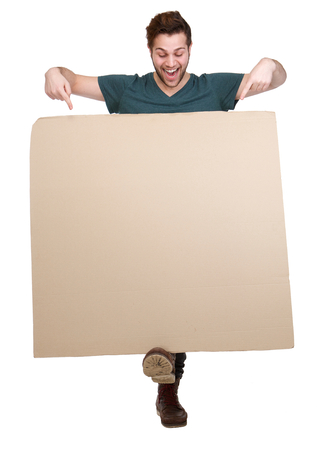 Full length portrait of a smiling man pointing fingers down to blank poster board on isolated white background photo