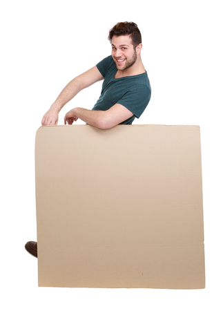 Full length portrait of a happy young man leaning on blank poster board on isolated white background photo
