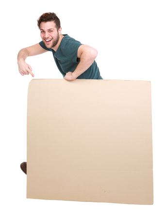 Full length portrait of a smiling man pointing to blank poster on isolated white background photo