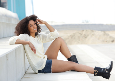Portrait of a beautiful young african american woman sitting outdoors  Fashion model relaxing photo