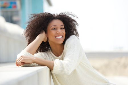 african beauty: Close up portrait of a smiling young woman relaxing outdoors  African beauty expressing positivity