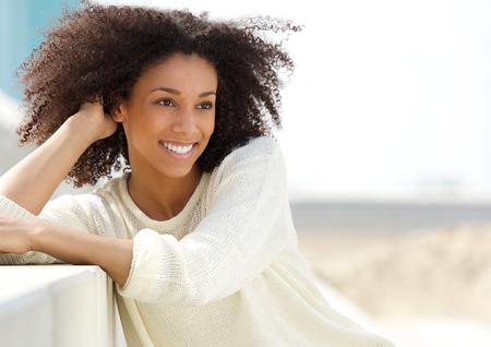 屋外でリラックスした美しい若いアフリカ系アメリカ人女性の肖像画を閉じる