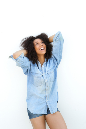 Portrait of a young african american woman smiling with hands in hair on white background photo