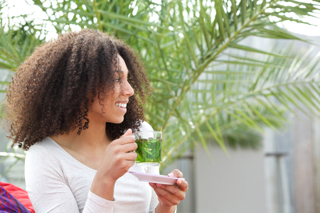 woman drinking tea: Close up portrait of a beautiful young african american woman drinking tea  Stock Photo