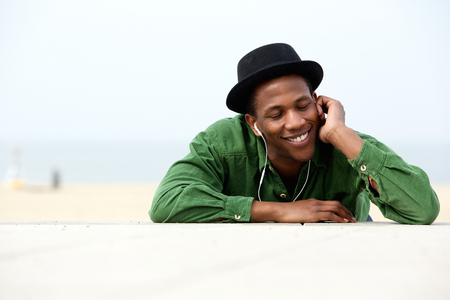 Close up portrait of a handsome young man relaxing outdoors listening to music on earphones  Stock Photo