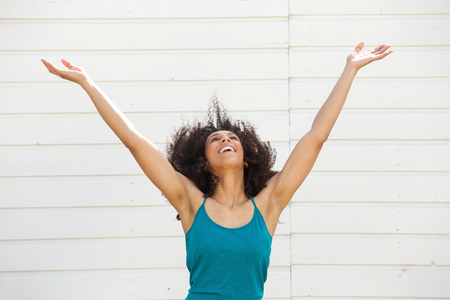 outstretch: Portrait of a young woman looking up with arms outstretched Stock Photo