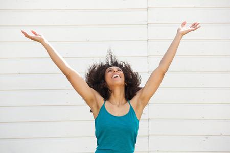 Portret van een jonge vrouw die omhoog met uitgestrekte armen Stockfoto