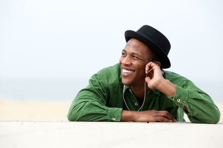 Close up portrait of a young man smiling and listing to music outdoors photo