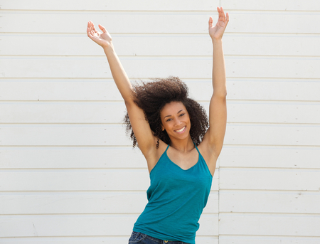 Portrait of a joyful young woman with arms up in the air Banco de Imagens