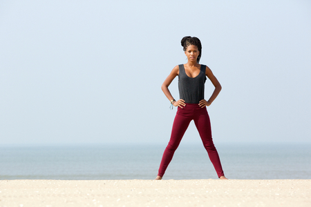 Portrait of one young woman exercising at the beach  photo