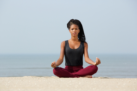 Portrait of a beautiful black woman sitting in yoga lotus pose at the beach