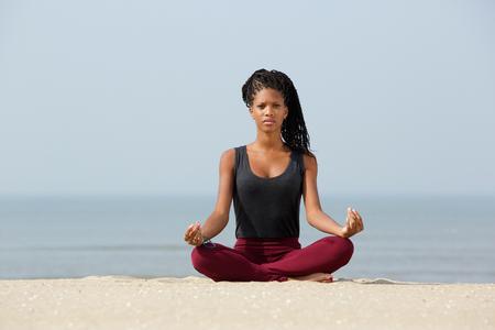 Portret van een mooie zwarte vrouw zitten in yoga lotus houding op het strand