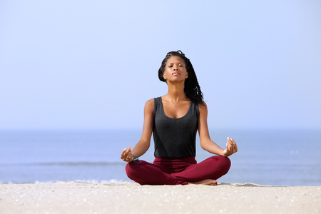 Portrait of a beautiful young woman sitting in yoga pose at the beach  Stock Photo