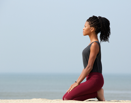 Side view portrait of a young woman meditating at the seaside