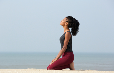 kneeling woman: Portrait of a beautiful young african american woman meditating at the beach enjoying summer