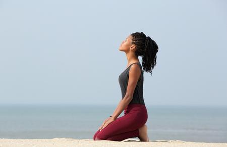 mujer arrodillada: Retrato de una mujer hermosa mujer afroamericana meditando en la playa disfrutando del verano