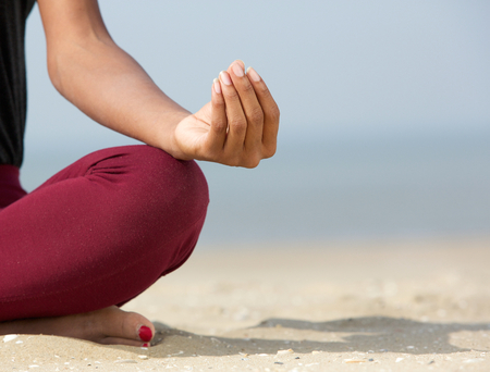 Close up portrait of young woman in lotus position with yoga hands at the beach