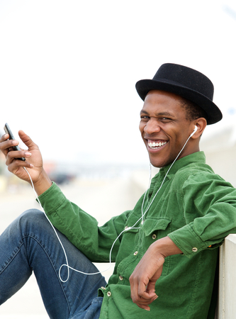 Portrait of a young man smiling outdoors with mobile phone and earphones photo
