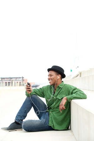 Portrait of a handsome black man with mobile phone and earphones photo