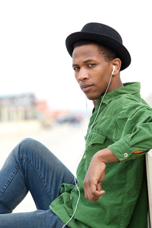 Close up portrait of a handsome young black man listening to music with earphones outdoors photo