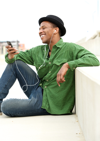Portrait of a happy young man listening to call on mobile phone with earphones photo