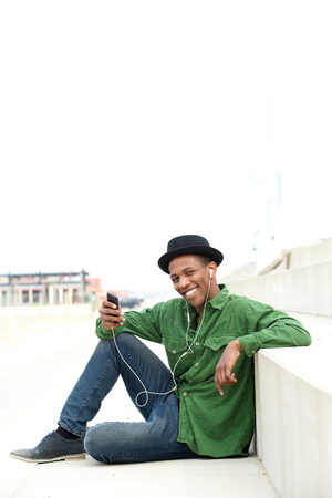 Portrait of a young man relaxing outdoors listening to music with mobile phone and earphones photo