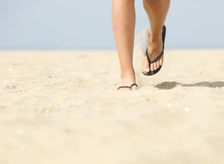 flip flops: Low angle view of woman feet walking forward in flip flops on beach Stock Photo
