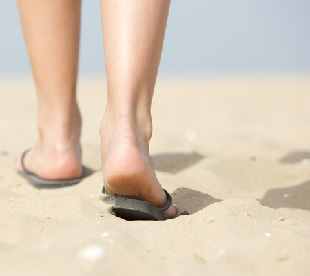 Close up from behind rear view woman walking in slippers on sand at beach photo