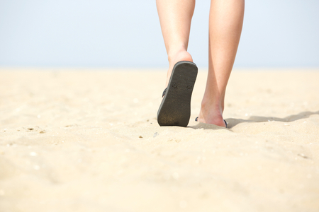 Close up feet in sandals walking on sand at the beach photo