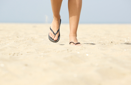 8ed64ed7a472 Close up low angle front view of woman walking on beach with flip flops