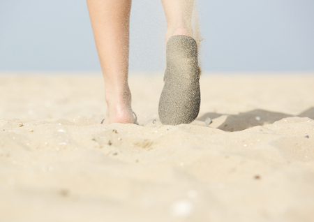 Low angle from behind view of woman walking with flip flops on beach photo