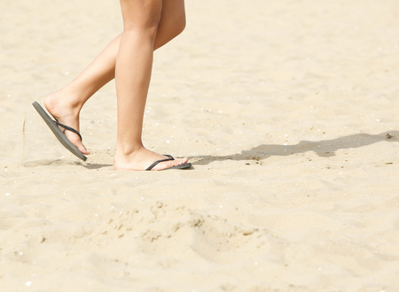 flip flops: Side view of young woman walking on beach with flip flops Stock Photo