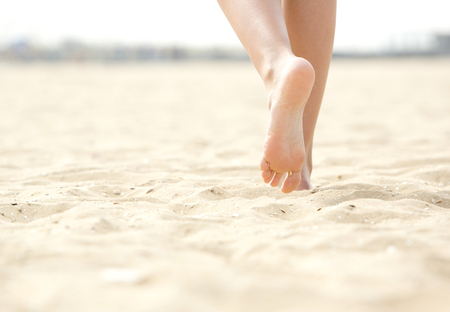 young girl feet: Close up low angle woman barefoot walking on beach